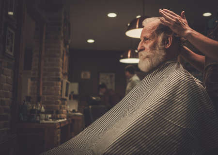 Senior man visiting hairstylist in barber shop. Banque d'images