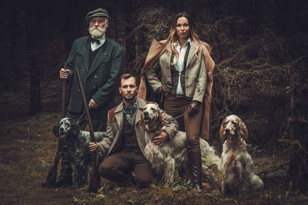 Group of multi-age hunters with dogs and shotguns in a traditional shooting clothing on a dark forest background. Stock Photo - 61733221