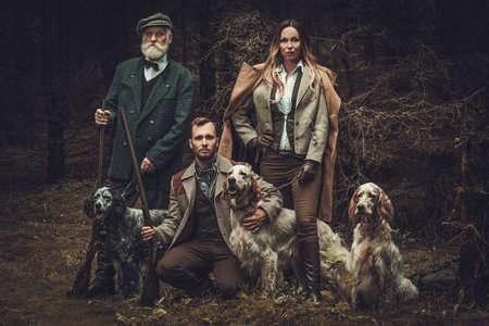 Grupa myśliwych wielu wiekowych z psami i strzelby w tradycyjnych strojach fotografowania na ciemnym tle lasu.