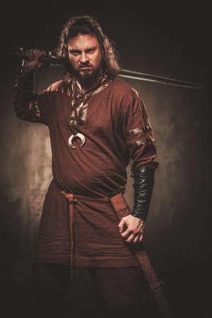 Serious Wikinger mit Schwert in einem traditionellen Krieger Kleidung, auf einem dunklen Hintergrund aufwirft.
