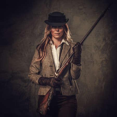 Dame met jachtgeweer van het wilde westen op een donkere achtergrond. Stockfoto