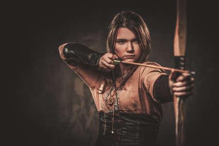 viking sérieux avec arc et flèche dans un vêtement de guerrier traditionnel, posant sur un fond sombre.