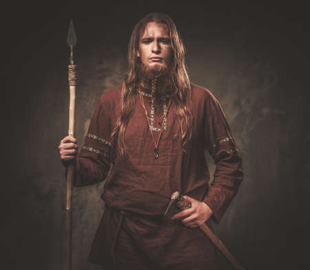 Serious Wikinger mit einem Speer in einem traditionellen Krieger Kleidung auf einem dunklen Hintergrund.
