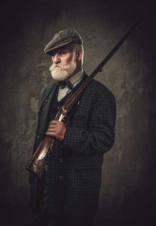 cazador mayor con una escopeta en una ropa tradicional de tiro sobre un fondo oscuro.