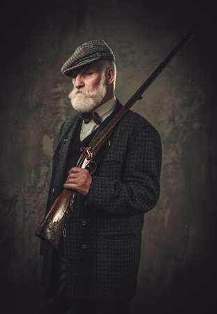 Senior hunter with a shotgun in a traditional shooting clothing on a dark background. Stock Photo