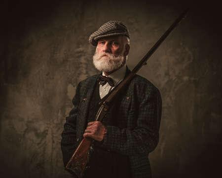 Senior jager met een shotgun in een traditioneel schieten kleding op een donkere achtergrond.