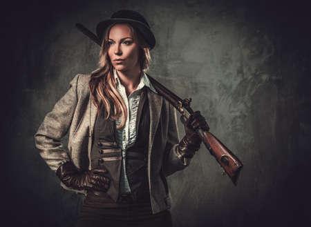 Lady with shotgun from wild west on dark background.