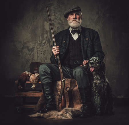 Senior hunter with a english setter and shotgun in a traditional shooting clothing on a dark background. Reklamní fotografie