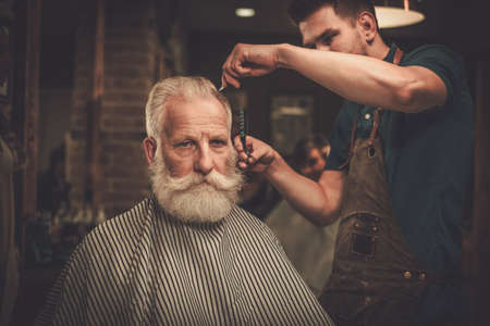 Senior man visiting hairstylist in barber shop. 스톡 콘텐츠