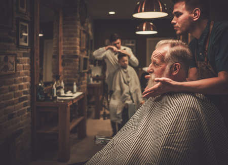 Senior man visiting hairstylist in barber shop. Reklamní fotografie
