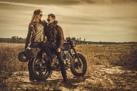 Young, stylish cafe racer couple on the vintage custom motorcycles in a field. Zdjęcie Seryjne - 63375021