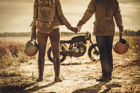 Young, stylish cafe racer couple on the vintage custom motorcycles in a field. 免版税图像 - 63375081