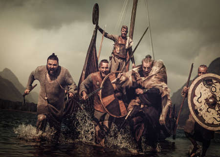Vikings warriors in the attack, running along the shore with Drakkar on the background. Standard-Bild