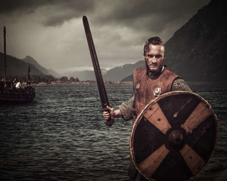 Serious viking warrior in the attack, standing along the shore with Drakkar and mountains on the background. Stock Photo