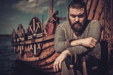 Serious viking warrior with axe standing near Drakkar on the seashore.