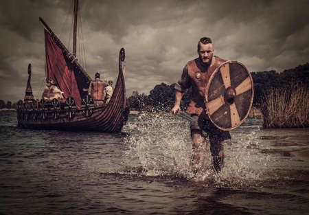 Serious viking warrior in the attack, running along the shore with Drakkar on the background. Stock Photo