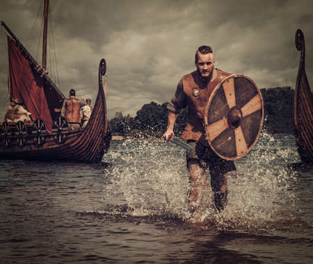 Serious viking warrior in the attack, running along the shore with Drakkar on the background. 免版税图像