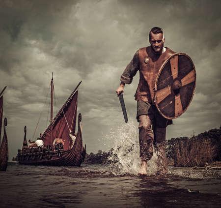 배경에 Drakkar와 해안을 따라 실행하는 공격에 심각한 바이킹 전사.