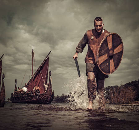 Serious viking warrior in the attack, running along the shore with Drakkar on the background. Stock fotó
