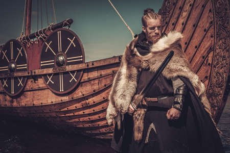 Serious viking warrior with sword standing near Drakkar on the seashore. Фото со стока