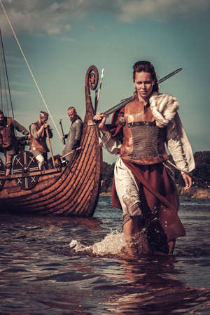 배경에 Drakkar와 함께 해안을 따라 걷고 칼을 자신감이 바이킹 여자.