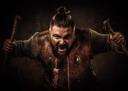 Angry viking with axes in a traditional warrior clothes, posing on a dark background.