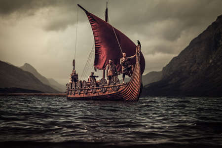 Group of vikings are floating on the sea on Drakkar with mountains on the background. Stock Photo