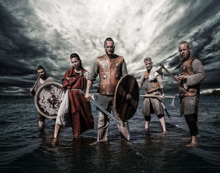 A group of armed Vikings, standing on the river shore with cloudy background.