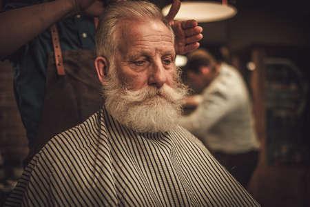 Senior man visiting hairstylist in barber shop. Stok Fotoğraf