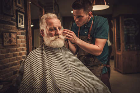 Senior man visiting hairstylist in barber shop. Foto de archivo