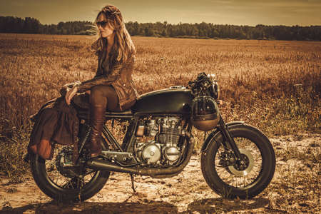 Young, stylish woman on the vintage custom cafe racer in a field. Zdjęcie Seryjne