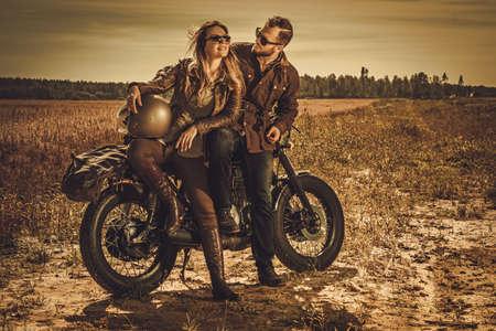 Jonge, stijlvolle cafe racer paar op de vintage custom motorfietsen in een veld.