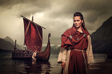 Confident viking woman with sword and shield standing near Drakkar on the seashore. Zdjęcie Seryjne - 64798117