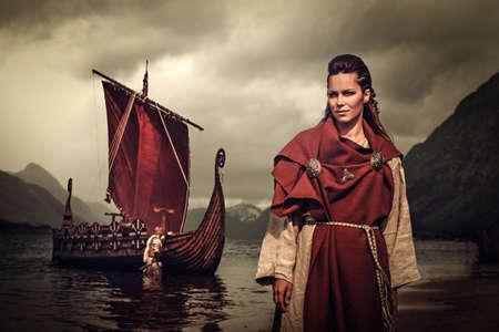 Zelfverzekerd viking vrouw met zwaard en schild staan in de buurt Drakkar aan de kust.