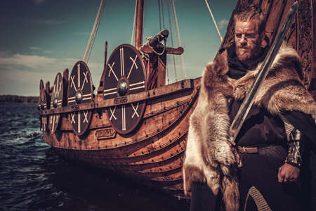 Serious viking warrior with sword and shield standing near Drakkar on the seashore.