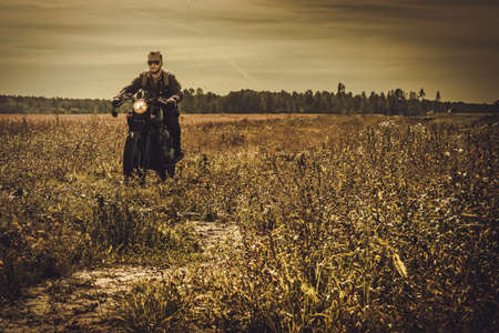 Young, stylish man on the vintage custom cafe racer in a field. Stock Photo