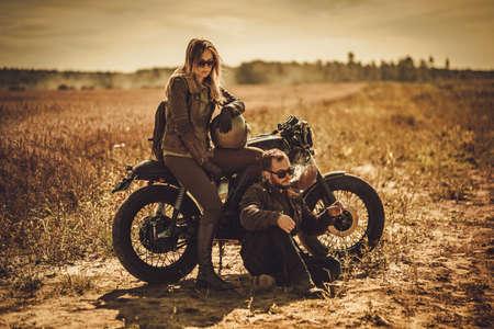 Junge, stilvolle Café-Rennläufer-Paar auf den Jahrgang benutzerdefinierte Motorräder in einem Feld.