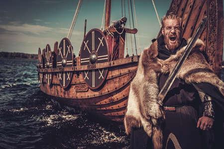 Ernstige viking warrior met zwaard en schild staan in de buurt Drakkar aan de kust. Stockfoto