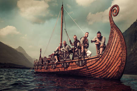 Group of vikings are floating on the sea on Drakkar with mountains on the background. 免版税图像