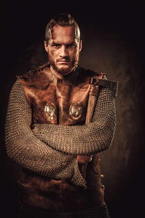 Ernstige viking in een traditionele krijger kleding, die zich voordeed op een donkere achtergrond. Stockfoto