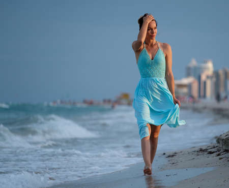 Beautiful woman walking along the South beach, Miami, USA