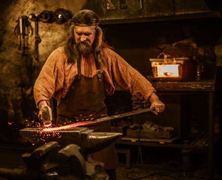 Senior blacksmith forging the molten metal on the anvil in smithy.