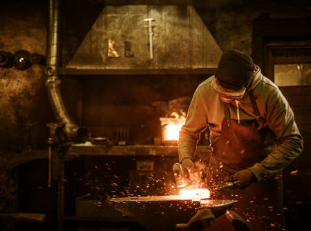 The blacksmith forging the molten metal on the anvil in smithy. Banco de Imagens - 64592910