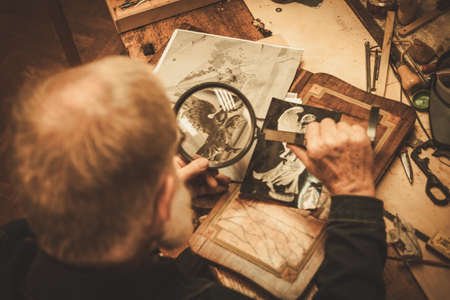 Senior restorer working with antique decor element in his workshop.