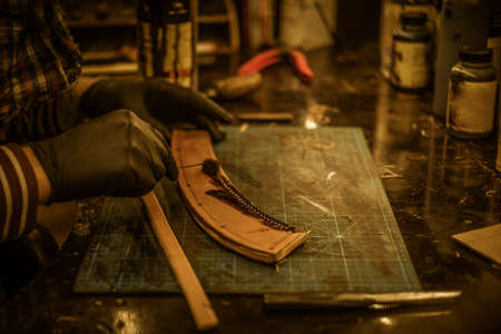 Blacksmith makes leather cover for axe.