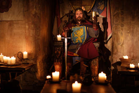 Old medieval king on the throne in ancient castle interior. Zdjęcie Seryjne - 64607867