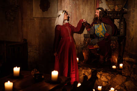 Medieval king with his queen in ancient castle interior. Reklamní fotografie - 64607919