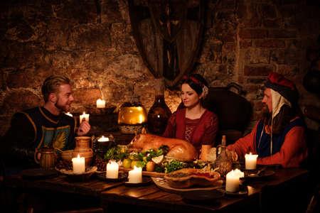 les gens médiévaux mangent et boivent dans l'ancienne cuisine, intérieur du château.