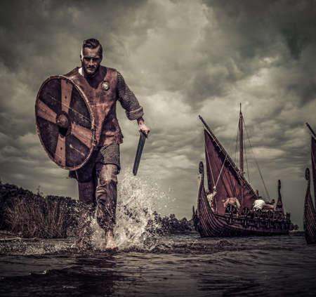 Guerrier viking en attaque, courant le long du rivage avec Drakkar en arrière-plan. Banque d'images - 69681951