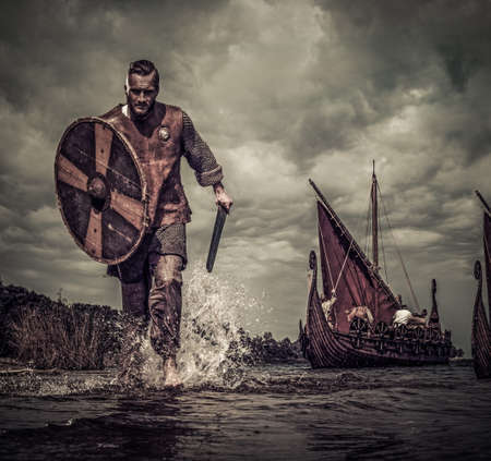 Viking warrior in attack, running along the shore with Drakkar on background.